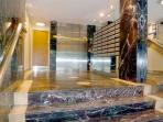 Marble style entrance hall to building with elevator