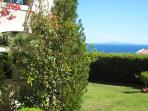 The sea view from the covered veranda of our lovely garden apt and the striking garden!