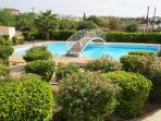 The large swimming pool at Peyia Paradise is surrounded by well-maintained gardens
