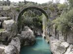 Ancient Roman bridge crossing over a small canyon in the local mountains. Fantastic scenery abounds