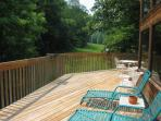 Relax on the spacious deck overlooking the 5-acre meadow and Rich Mountain.