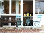 Patio area outside Crocus Cottage, with a sturdy wooden bench and a patio table and chairs.