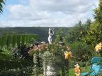 Blumen geschmückter Springbrunnen im Garten
