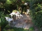 giardino con barbecue, tavolo e sedie