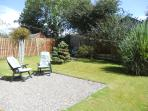 Rear garden graveled sitting area ideal for soaking up the sun with patio area in the corner