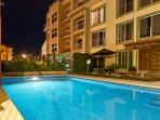 Common pool area at night lights out at ten,hasv table chairs and loungers,