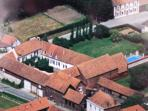 Aerial view of The Farmhouse, courtyard, barns, garden, pool - secure and private with gates shut.
