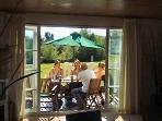 Patio doors onto a private decking area, with dining table and comfortable lounge area.