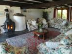 The spacious beamed sitting room with log stove