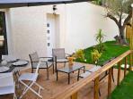Terrasse privative avec table, chaises, parasol et petit salon de jardin