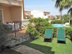 Sun bathe in comfort in the private garden next to the communial pool