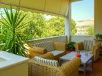 Shaded terrace with bamboo armchair setting and magnificent view at Trogir harbor
