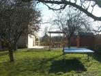 Winter sunlight in the garden with fruit trees, table tennis, BBQ and pergola