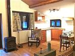Living room area with fully equipped kitchen and wood stove