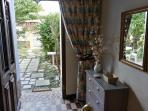 Depuis la maison, l'entrée avec vue sur le jardin clos, le portillon et la rue à sens unique