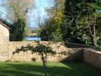 View from enclosed south garden over the moat, a source of the Avon and home to Doughton's duck