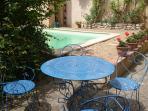 Coin repas avec table et parasol au bord de la piscine dans le jardin