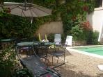 Coin repas avec table et parasol au bord de la piscine