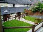 middle level of terraced garden to lawn looking at the rear of the cottage