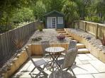 At the rear of Beach Cottage there is a breakfast patio and a summer house in the garden