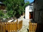 Rear enclosed private garden with impressive dry-stone walling and built-in bench