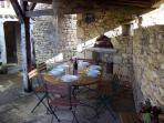 Terrasse semi couverte aménagée. Barbecue et espace repas pour 6 personnes