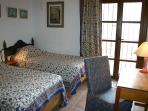 Twin bedroom with large fitted cupboards and writing desk; access to secluded back patio.