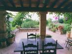 Porche y terraza en el jardin con mesa y balancines para comer/cenar/ desayunar