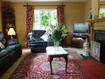 Large comfortable sitting room with TV/DVD and open fireplace.