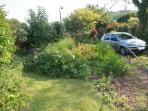 View from the kitchen showing the cottage garden and parking.