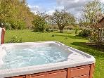 Hot tub behind main farmhouse and The Ayrshire apartment for shared use