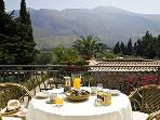 The breakfast area on the balcony, with panoramic views to the mountains.