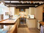 The kitchen has an induction hob, dishwasher, microwave and in the laundry, a fridge freezer.