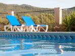 Exterior shot of 2 loungers by the pool - there are plenty of sun-loungers for all