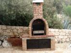 Outside barbecue and brick oven is conveniently located near the kitchen.