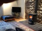 The lounge with its wood burning stove accommodates up to 8 adults and 2children