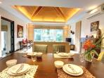Open plan living and dining area overlooking the pool and garden