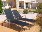 Patio area adjacent to pool with sun loungers