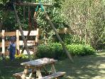 Play area in garden includes swings and playhouse, large garden and fields with access