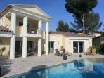 Facade de la maison avec la terrasse couverte et la piscine.