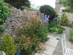 the cottage garden is surrounded by a 6 foot dry stone wall