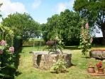 Vue de la terrasse sur le jardin avec puits bien recouvert pour la sécurité