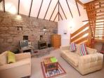 Smiddy living room with beams, feature stone wall, double sofa bed and stairs to galleried bedroom