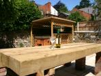 Luxury hot tub in enclosed landscaped garden with wooden seating and cycle storage.
