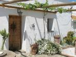 Front of house showing traditional rustic door and grapevine shade