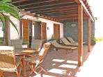 Large covered terrace with teak dining furniture and sunloungers with high quality cushions