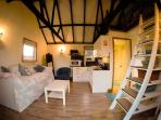 Vaulted ceiling, hand crafted mobile stairs to mezzanine, cosy furniture, warmth & light