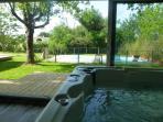 Vue de la piscine depuis le coin détente et son jacuzzi