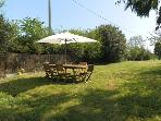 Garden dining next to BBQ facilities & outdoor house with guest kitchen facilities.