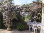 Garden room under  pergola covered in flowering climbers with barbecue and dining table